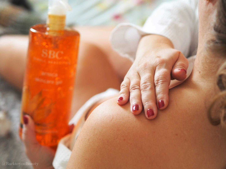 applying sbc arnica skincare gel to shoulder